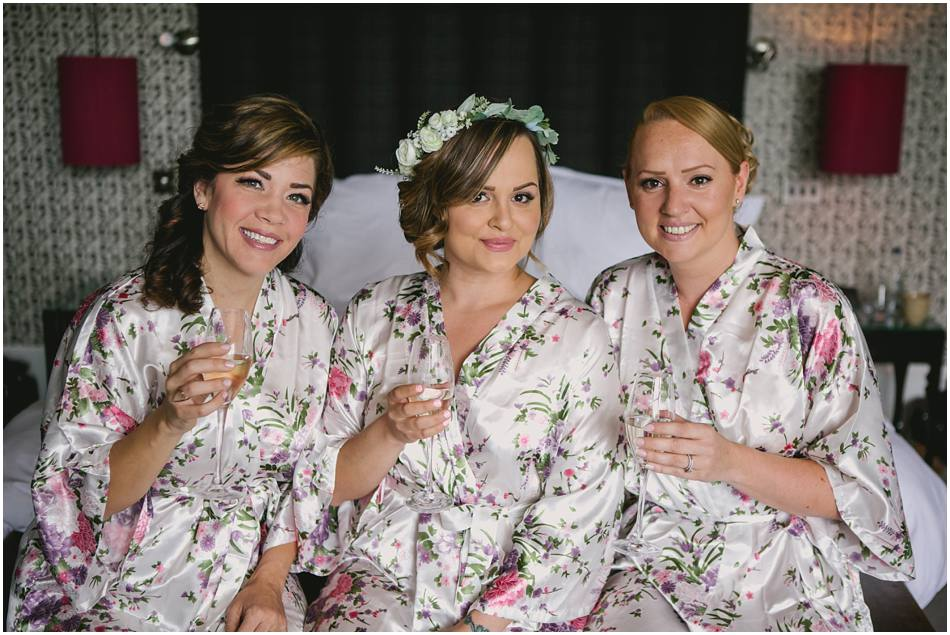 Bride in flower crown with her Bridesmaids wearing floral robes, at Hampton Manor wedding
