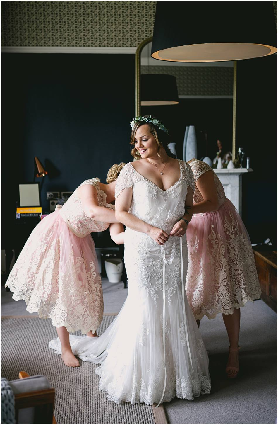 Bridesmaids in short pink lace dresses helping the Bride get ready on her wedding day