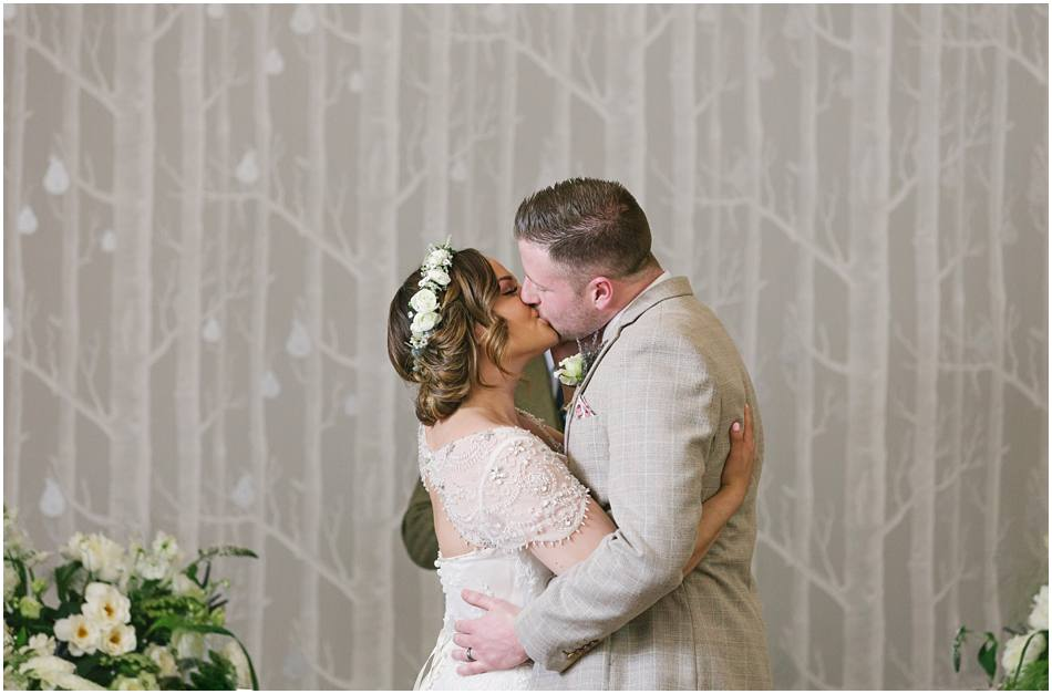 Bride and Groom kissing after the ceremony on their wedding day at Hampton Manor