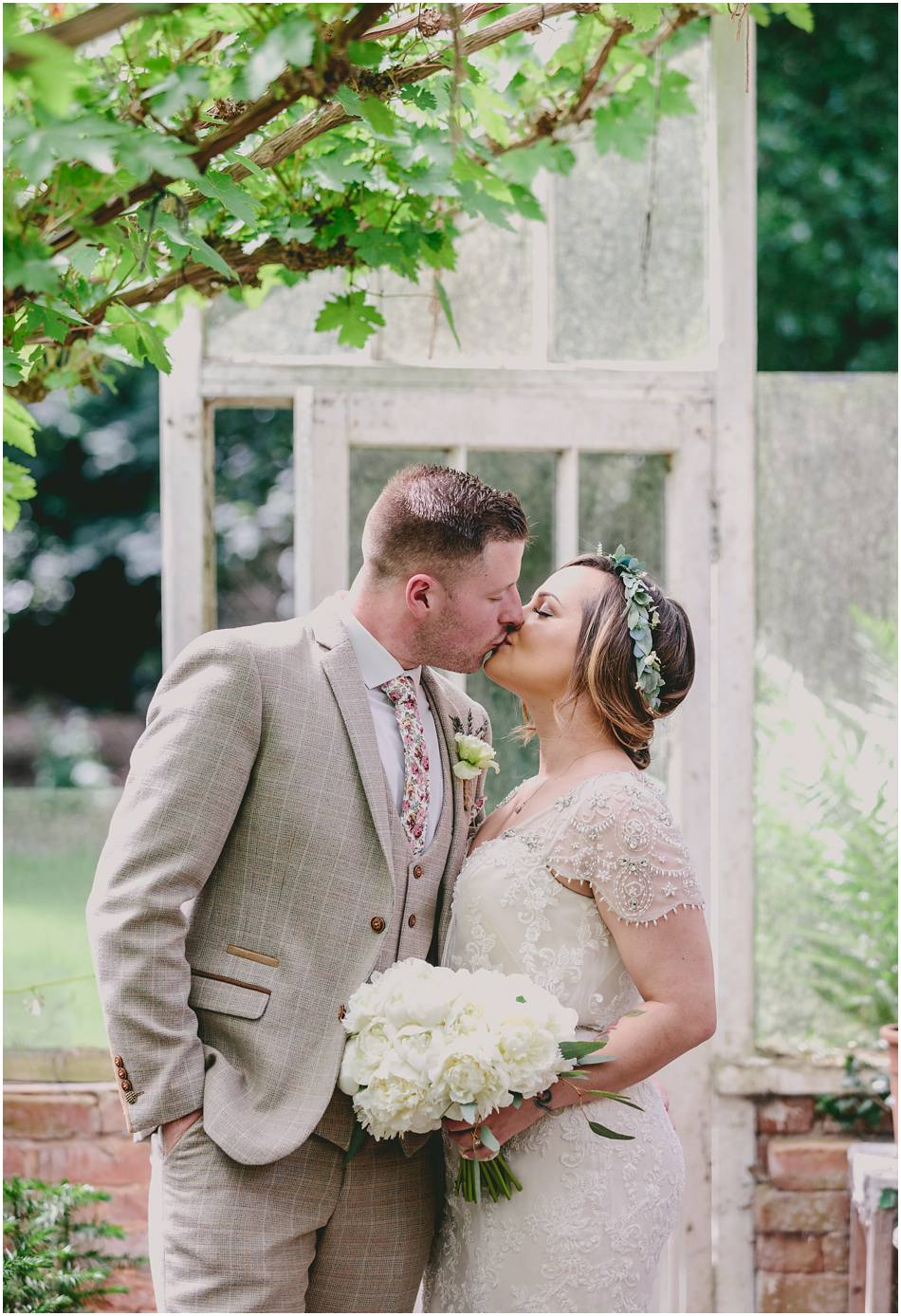 Bride and Groom kissing in the Hampton Manor greenhouses on their wedding day