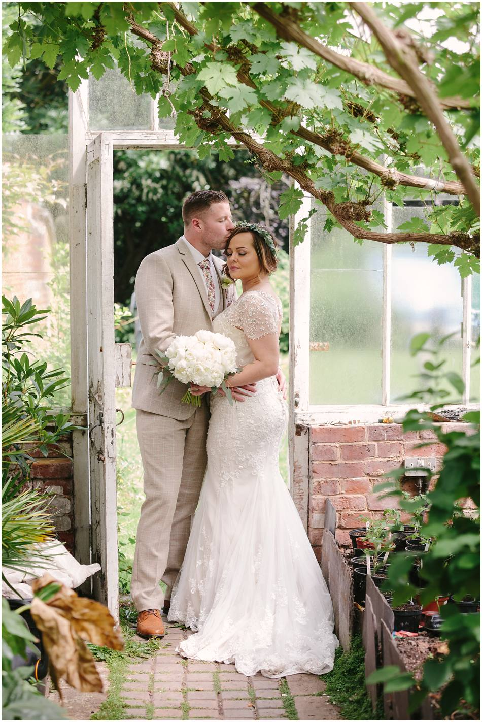 Bride with flower crown and Groom kissing in a greenhouse