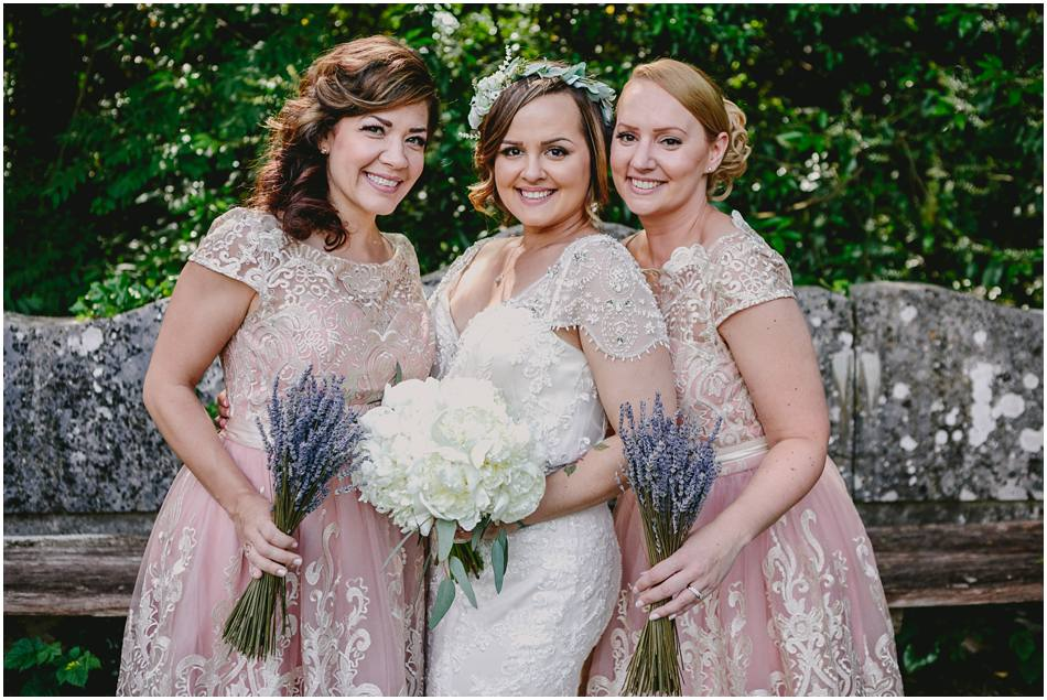 Portrait of a Bride wearing a flower crown with her Bridesmaids in short pink dresses with lace