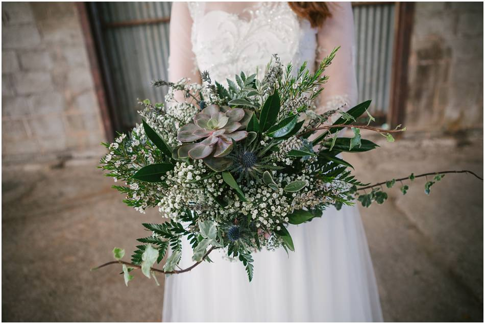 Bride holding a bouquet of succulents and foliage on her wedding day