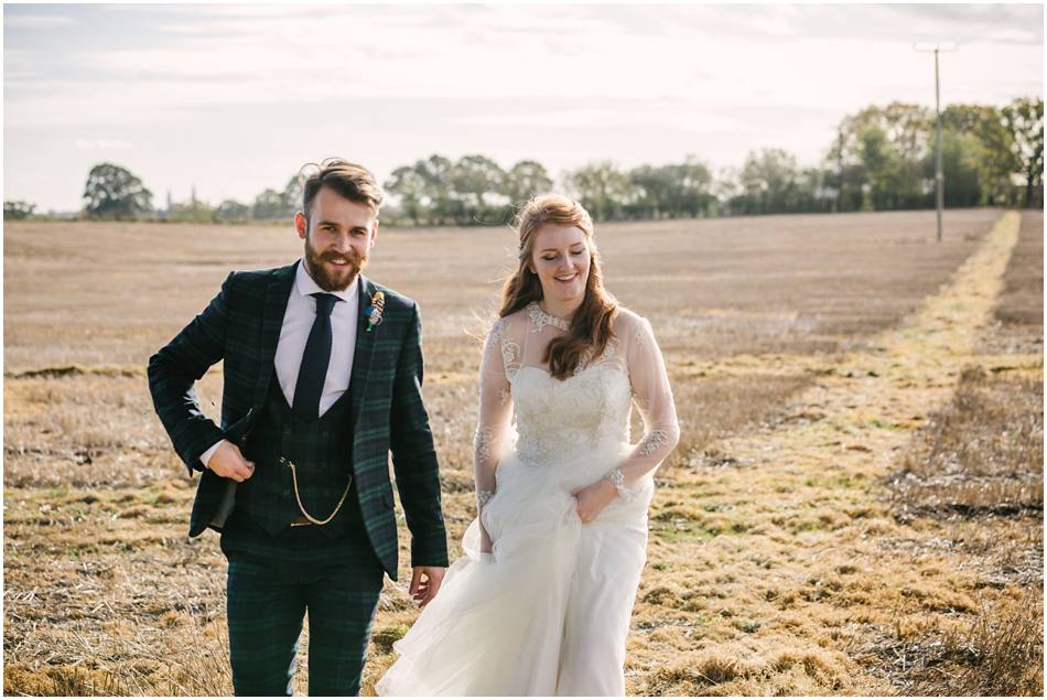 Couple walking in a cornfield at Curradine Barns; Groom with beard and tartan suit