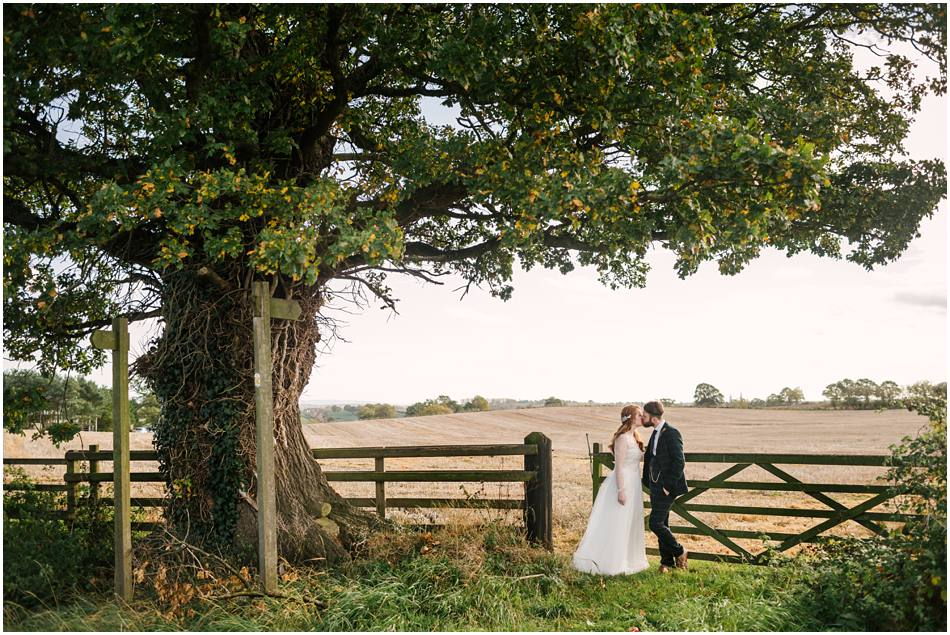 Curradine Barns wedding photography; Bride and Groom kissing by a gate