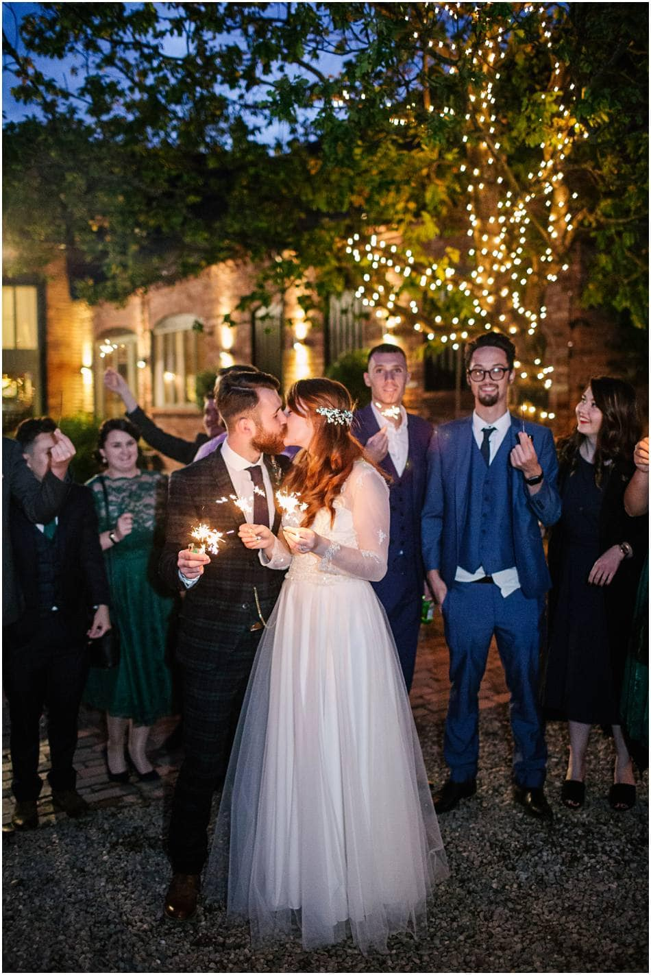 Bride and Groom holding sparklers and kissing at Curradine Barns