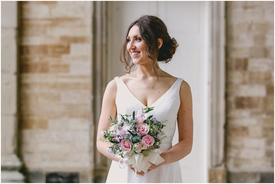 Compton Verney wedding photography; portrait of Bride holding bouquet of pink roses, with relaxed hair up hairstyle