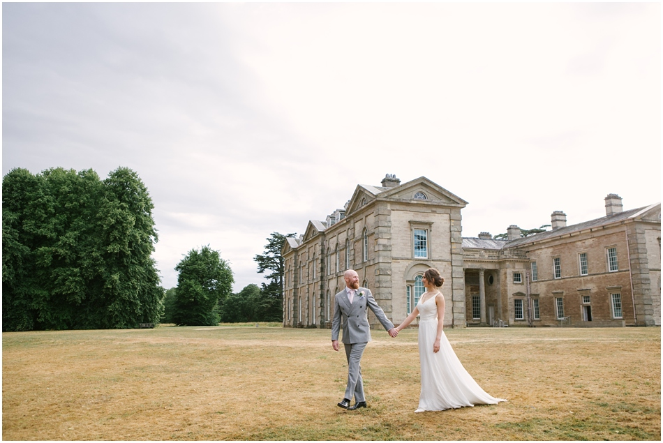 Compton Verney wedding photography; Bride and Groom walk holding hands with the house in the background