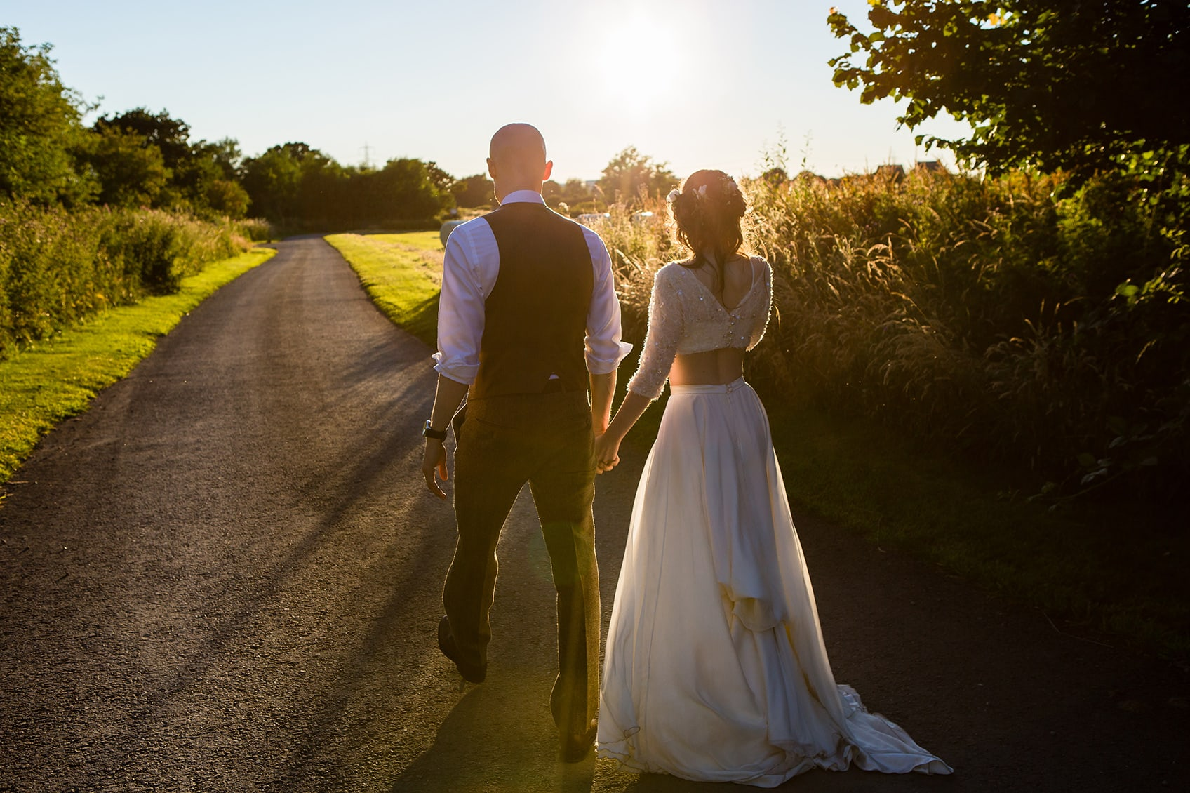 Shustoke Barn wedding photography; Couple holding hands walking