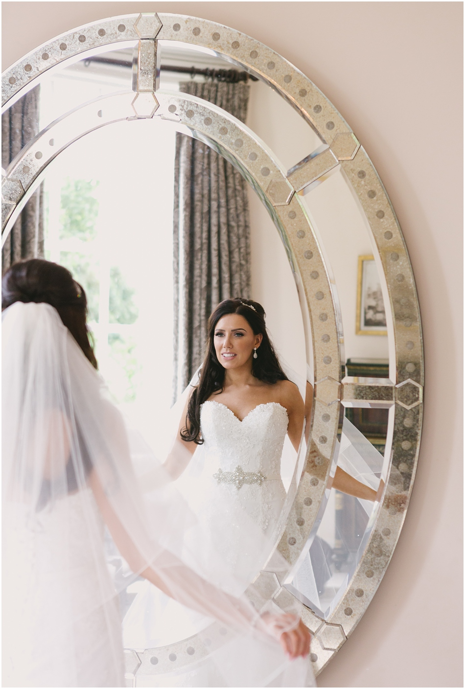 Romantic Iscoyd Park wedding; Bride looking in the mirror in the Bridal Suite