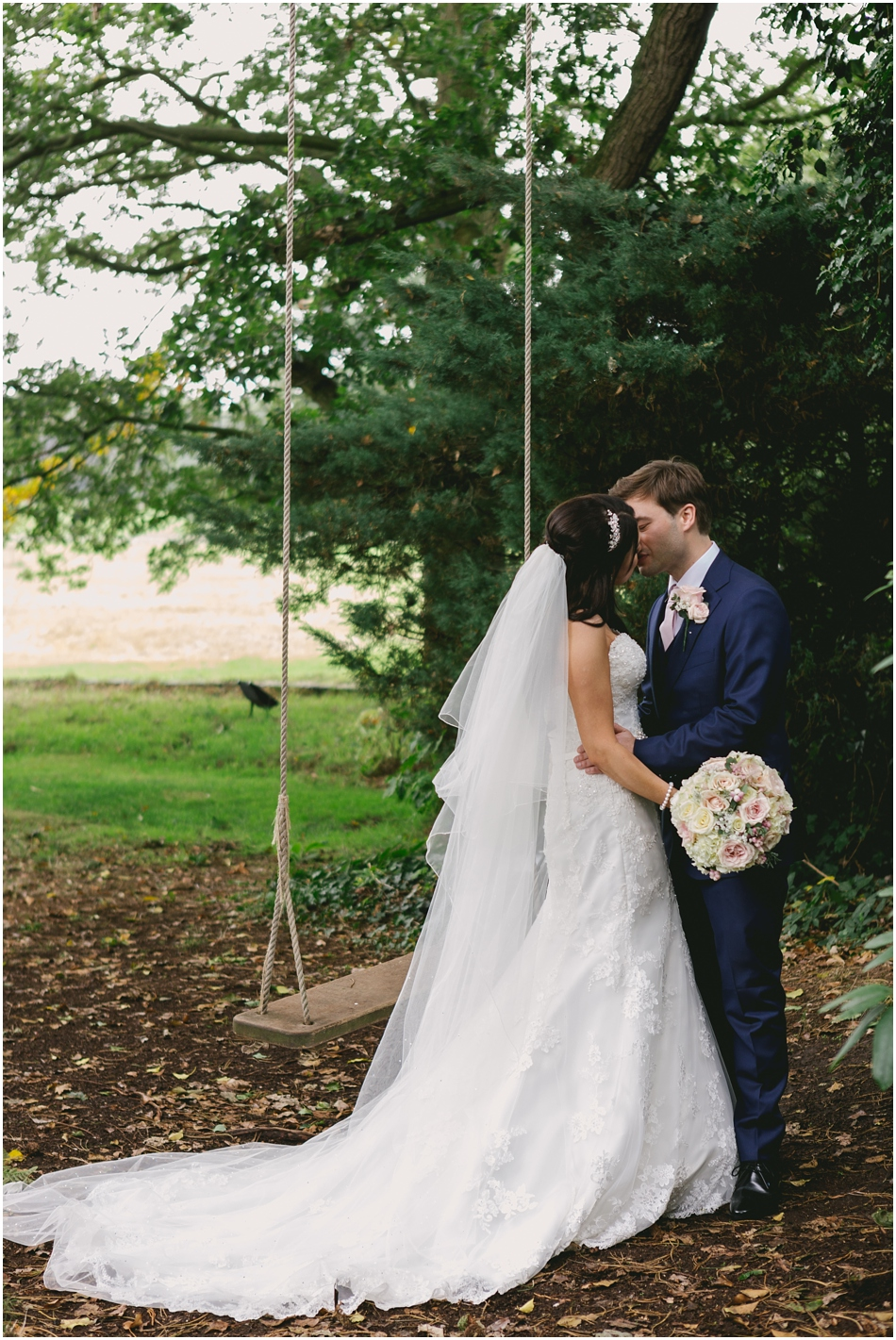 Romantic Iscoyd Park wedding; portrait of Bride and Groom kissing by the swing on their wedding day