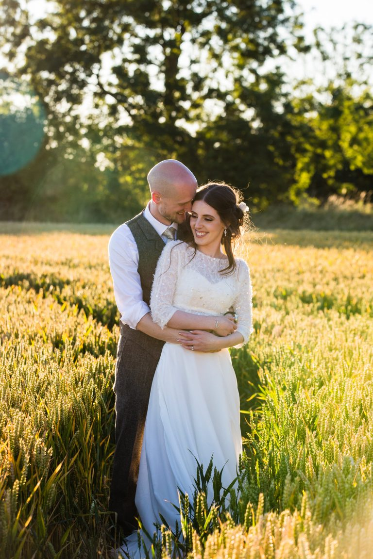 Shustoke Barn wedding photography; portrait of Bride and Groom in the cornfield ant sunset
