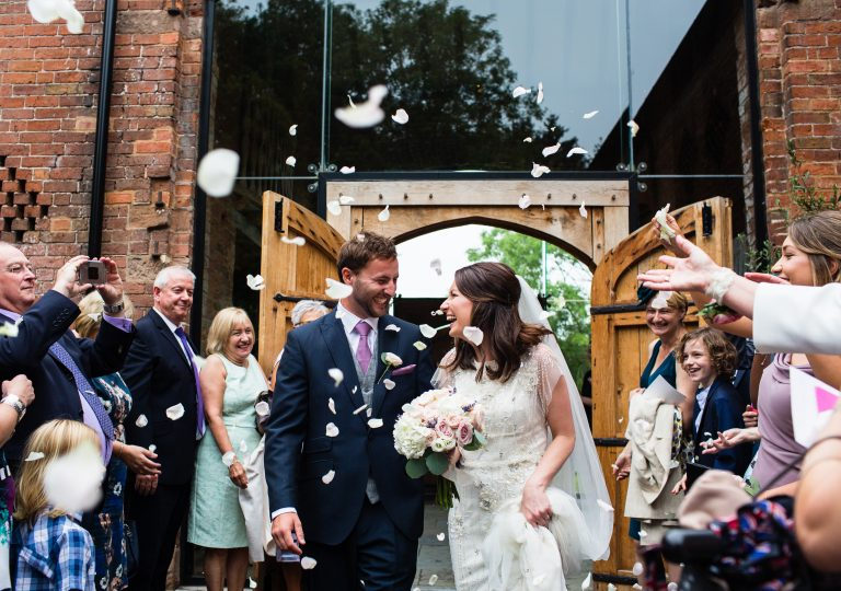 Shustoke Barn wedding photography; Bride and Groom with confetti