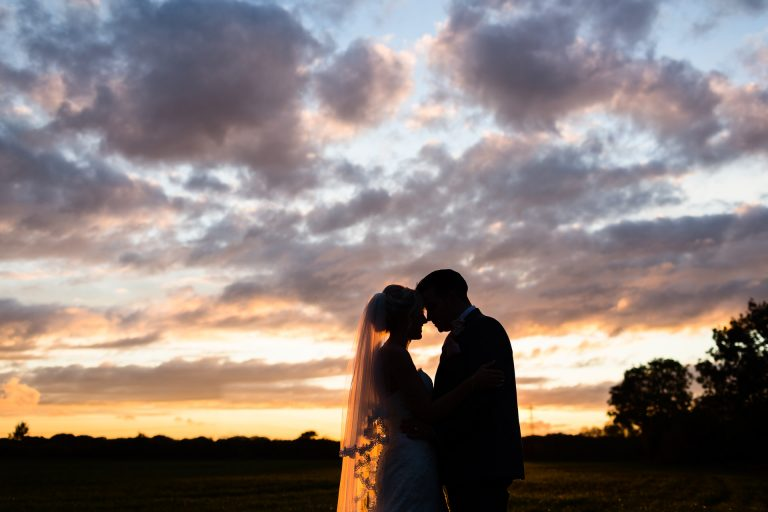 Shustoke Barn wedding photography; silhouette of Bride and Groom at sunset