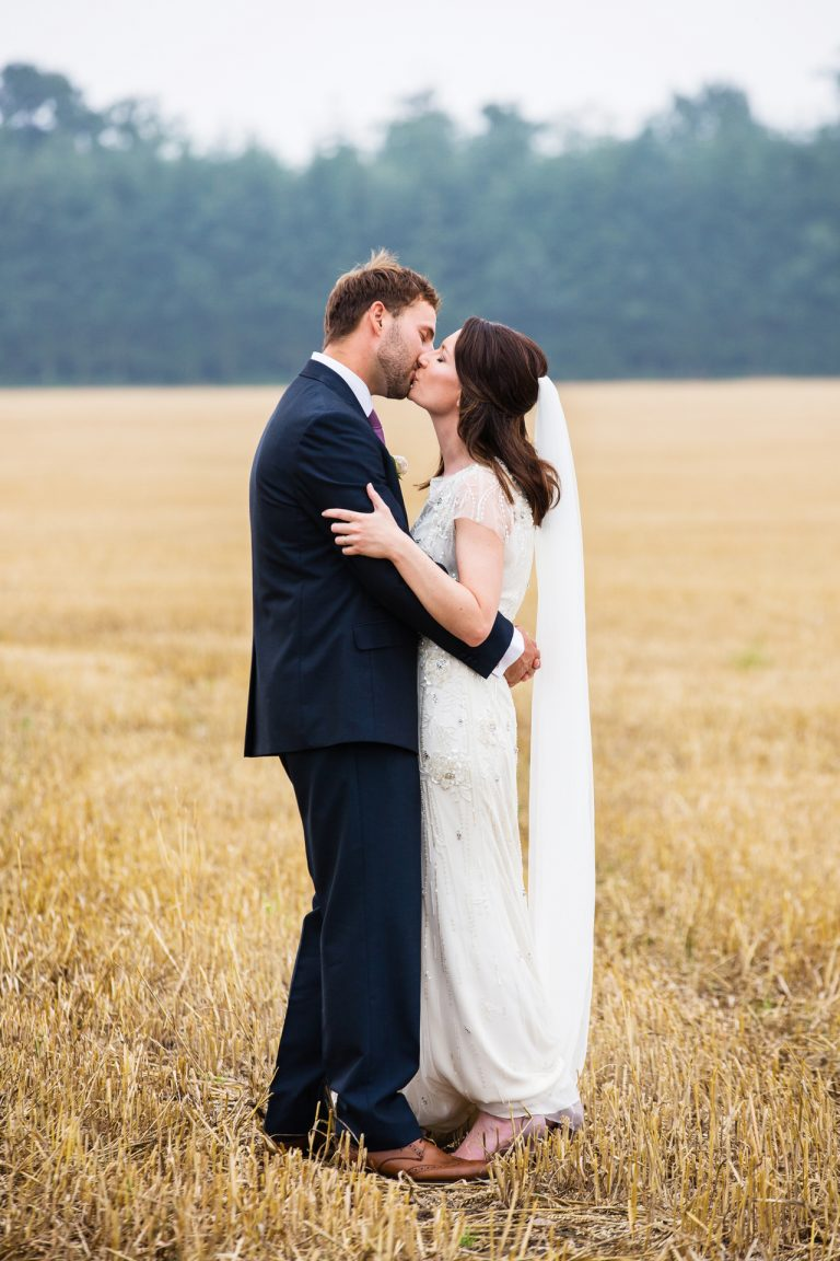 Shustoke Barn wedding photography; Bride and Groom kiss in a cornfield