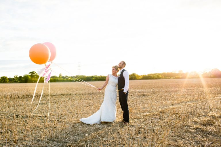 Shustoke Barn wedding photography; Bride and Groom with giant balloon
