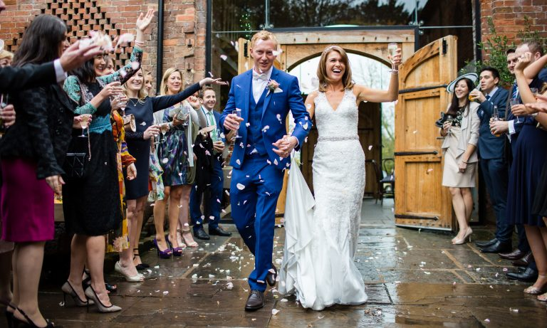 Shustoke Barn wedding photography; Bride and Groom walk out to confetti