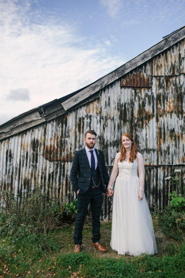 Bride in vintage wedding dress in front of barn