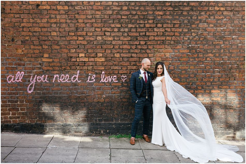 Hope Street Hotel wedding photography; Bride & Groom stand in front of Beatles lyrics wall