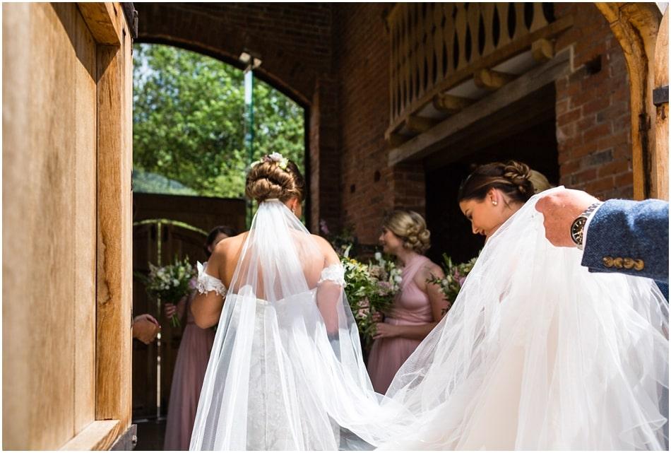 Bride entering Shustoke Barn on her wedding day