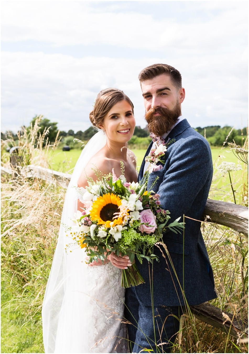 Groom with beard and wearing a dickie bow and Bride with rustic bouquet with sunflowers at Shustoke Barn