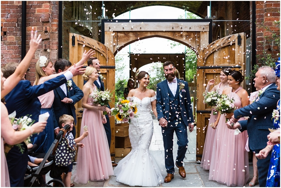 Couple walking out to confetti at Shustoke Barn Wedding