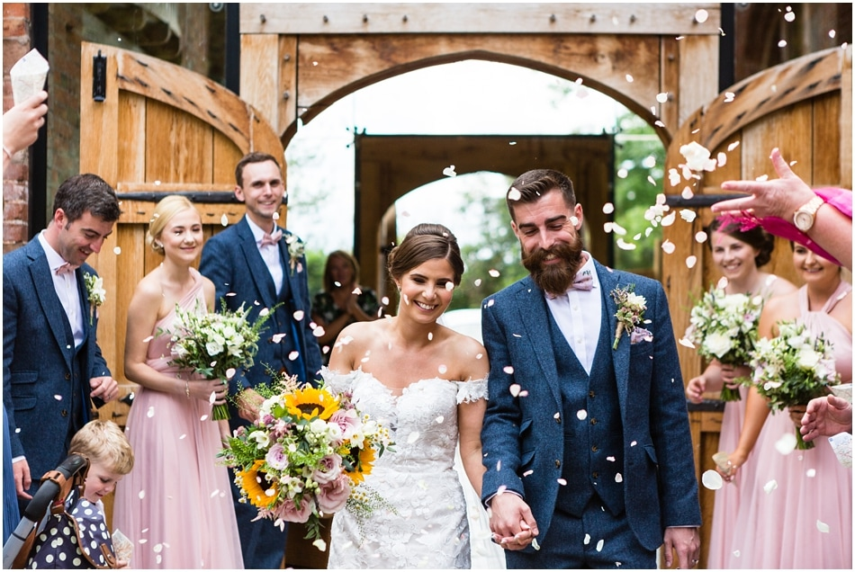 Dickie bow wearing bearded Groom with his Bride walking through confetti at Shustoke Barn