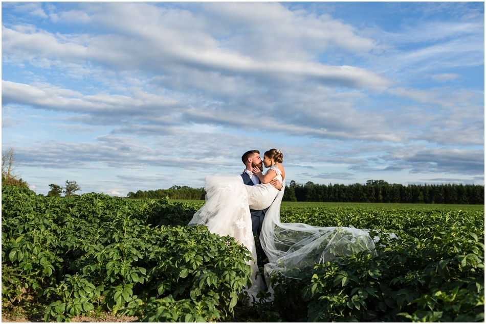 Shustoke Barn wedding photography; Groom carrying Bride through the fields