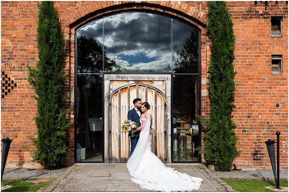 Shustoke Barn wedding photography; couple portrait in front of front doors