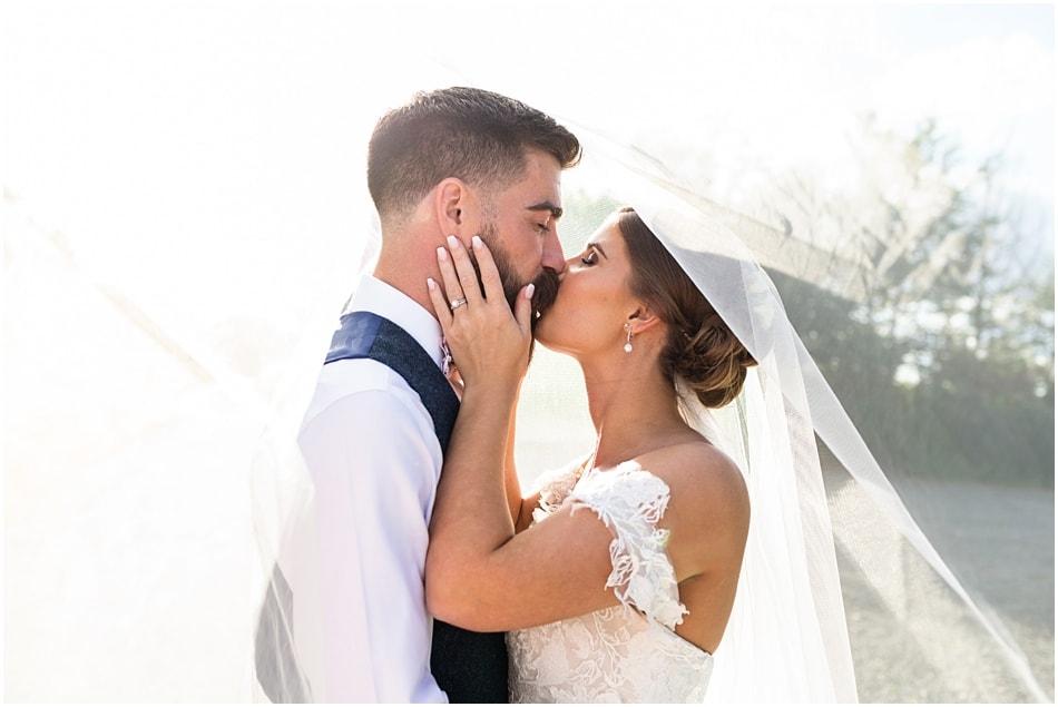 Shustoke Barn wedding photography; Bride and Groom kissing under veil
