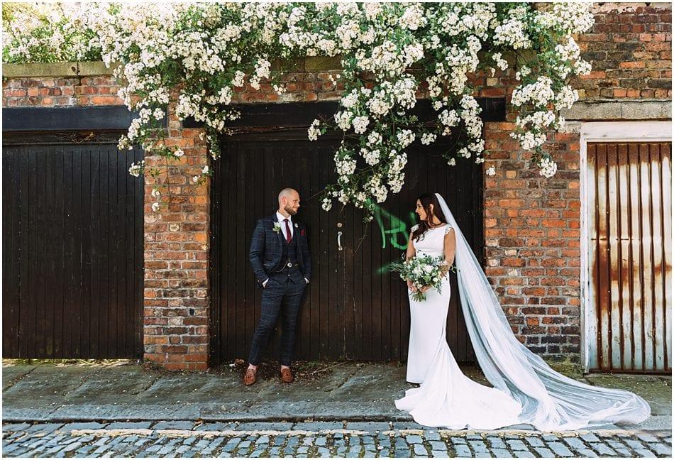 Siren wedding photography; Bride and Groom standing against garage doors
