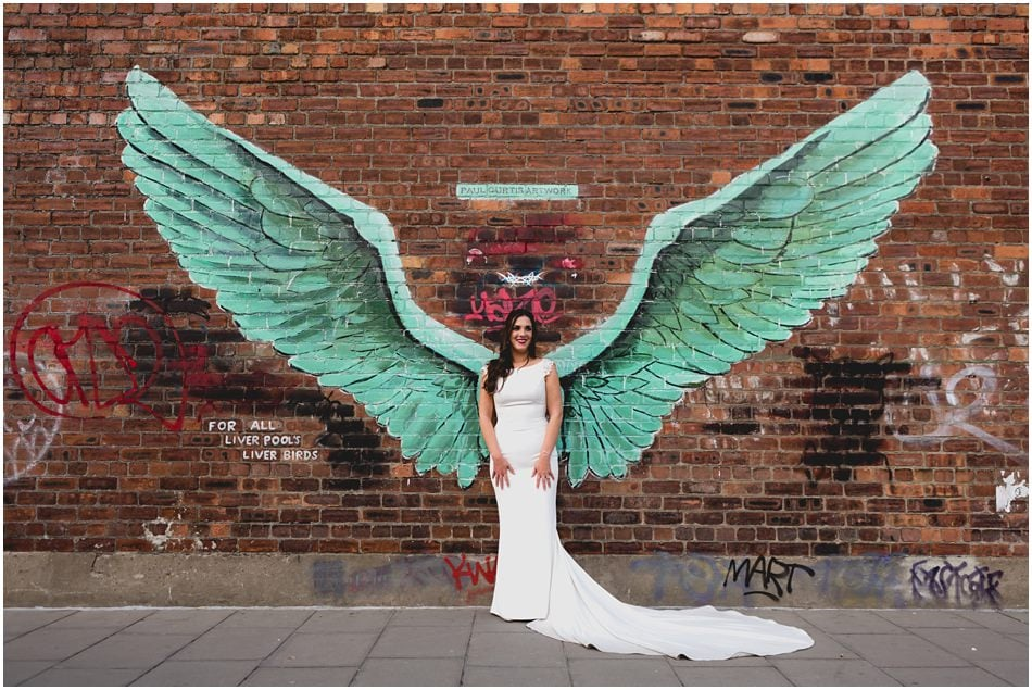 SIren Liverpool wedding photography; Bride with angel wings graffiti