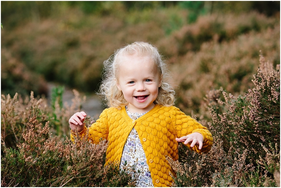 little girl laughing in the Autumn heather