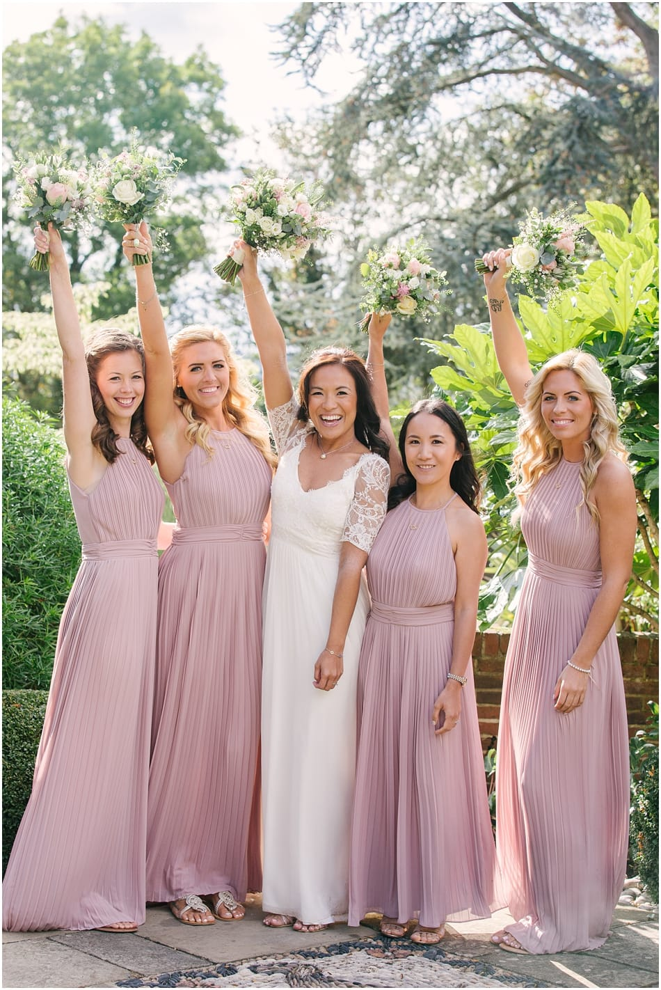 Bride and Bridesmaids wearing pink dresses with bouquets in the air at Gorcott Hall