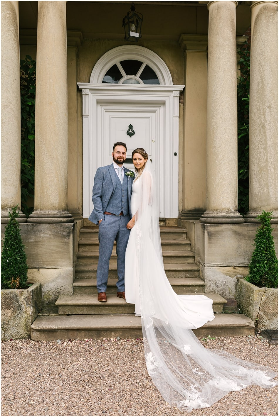 Couple pose on the front steps of Iscoyd Park on their wedding day