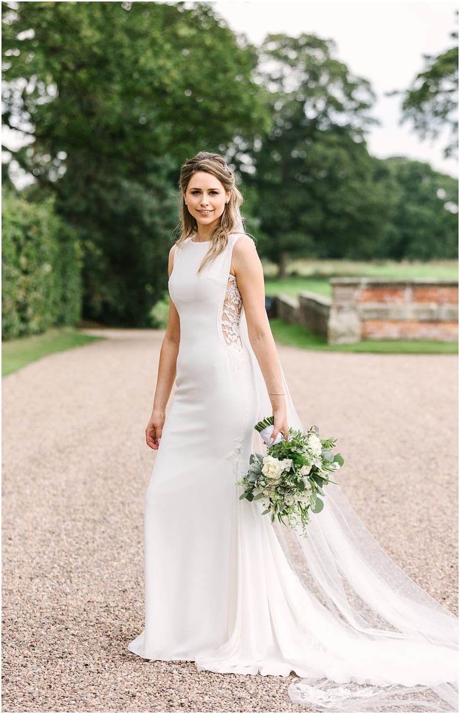Bride wearing Pronovias fitted dress with lace side panel at her Iscoyd Park wedding