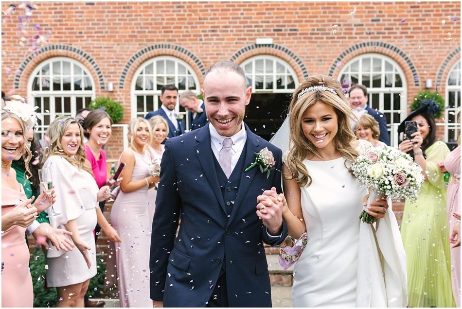 Alrewas Hayes wedding photography; couple walking through confetti