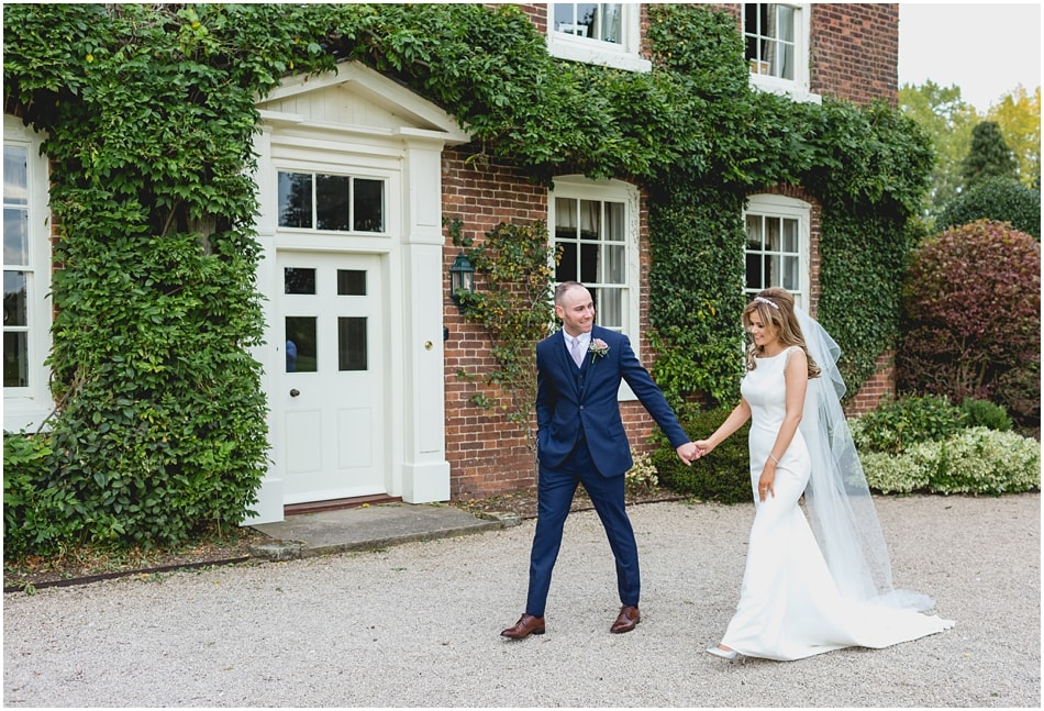 Documentary style wedding portrait of Bride and Groom walking at their country house wedding
