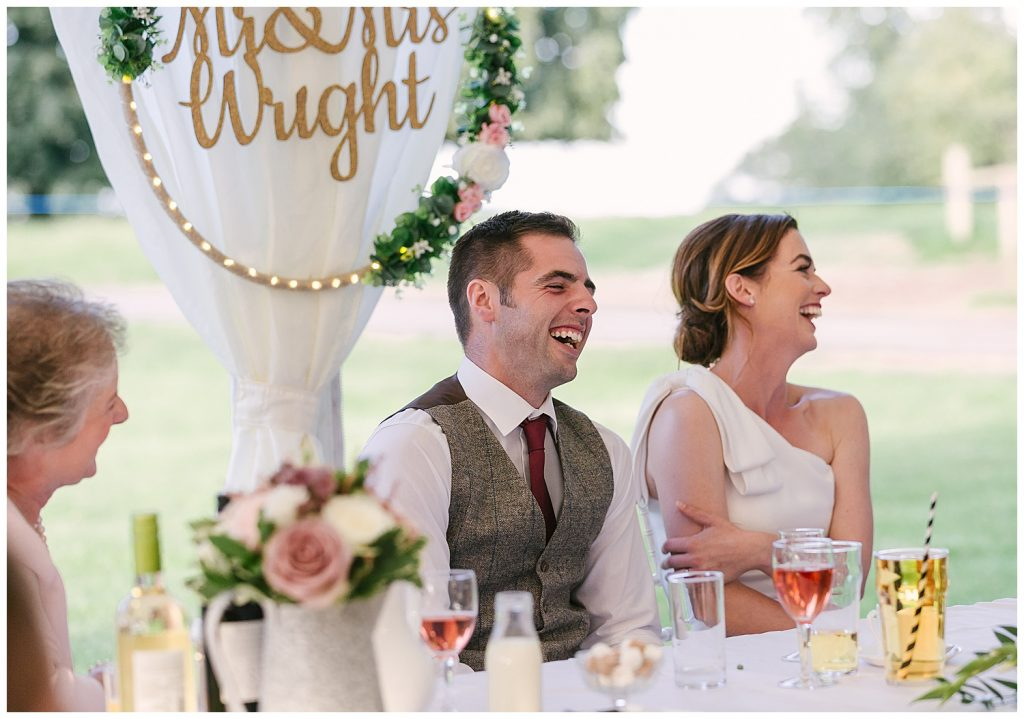 couple laughing during speeches on their wedding day