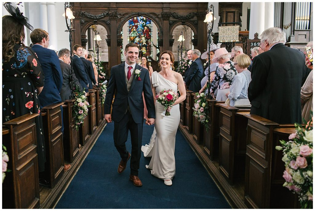 Smiling newlyweds walk down the aisle at Ingestre Church