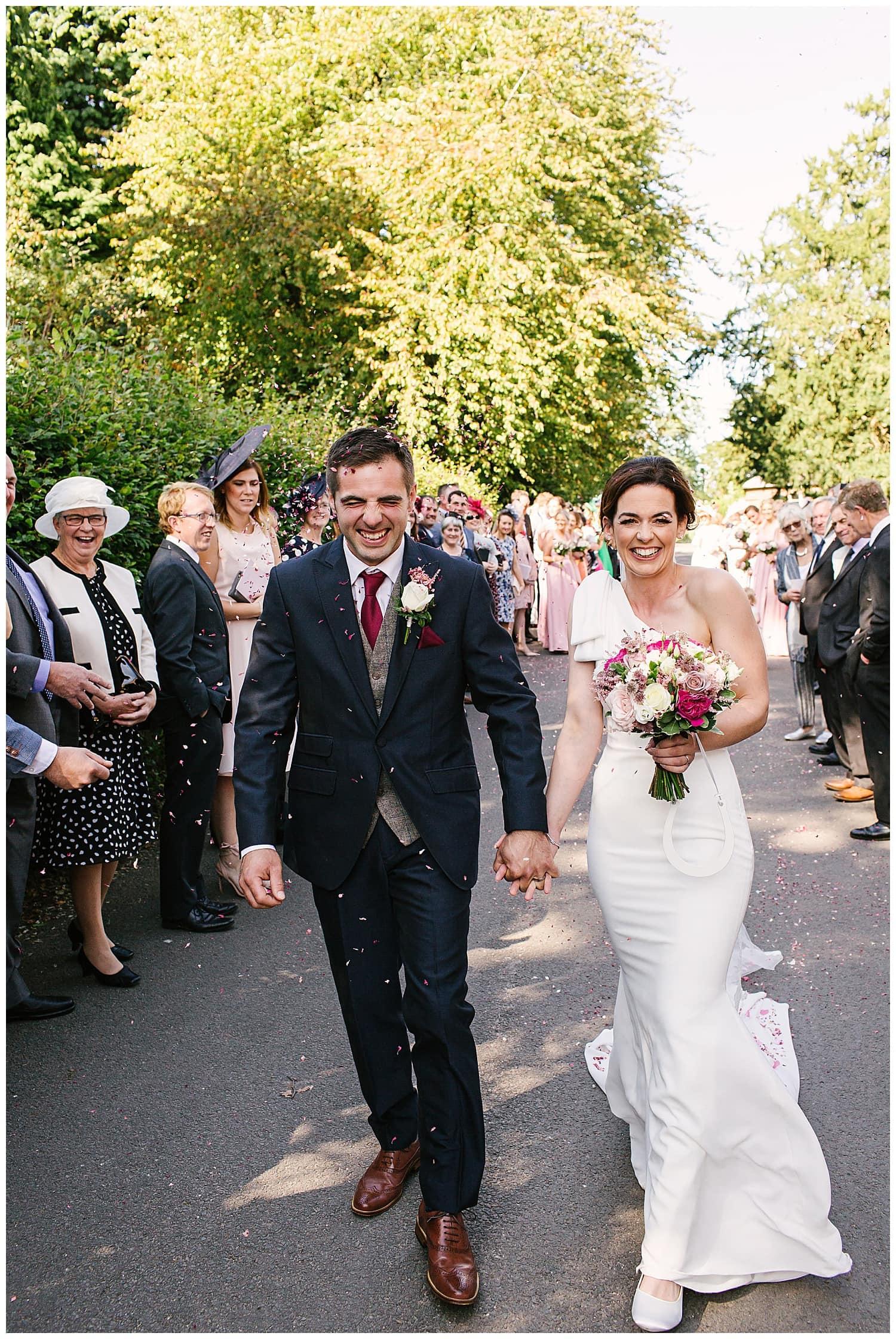 Newly married couple walking through confetti outside Ingestre Church, near Stafford