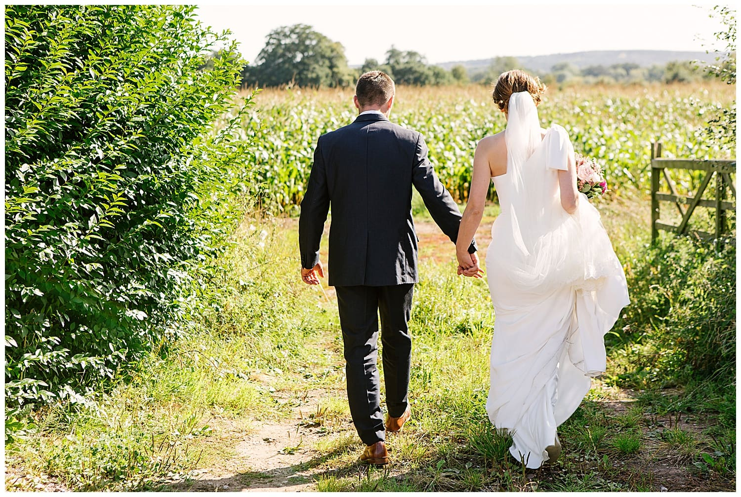 Newly married couple holding hands walk into cob field in rural Staffordshire