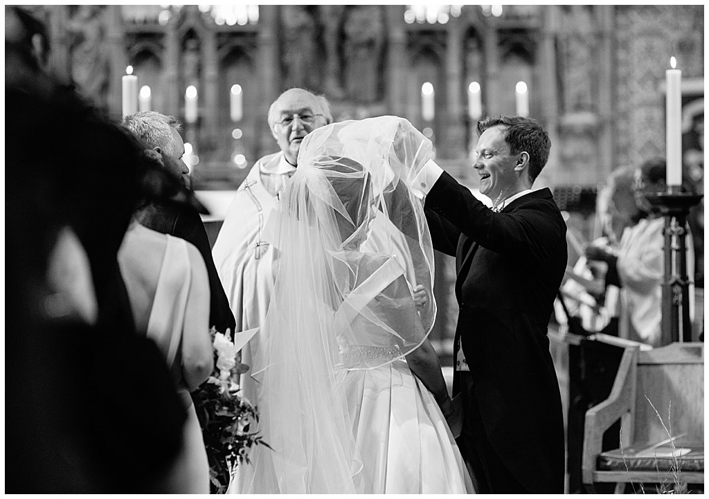 Groom lifts the Bride's veil