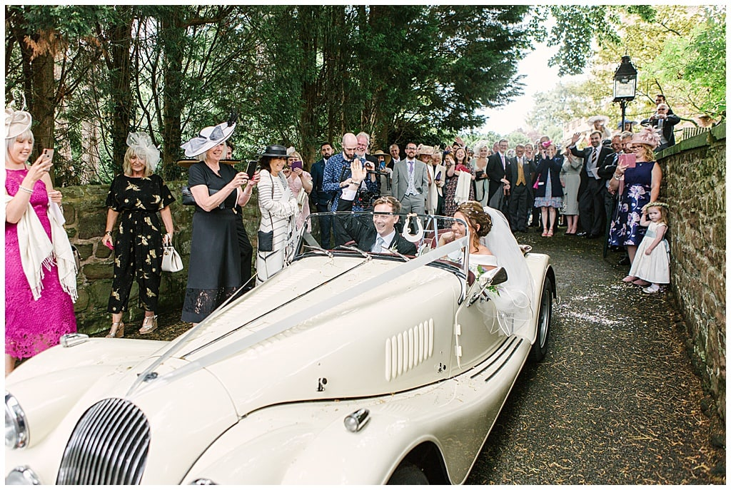 Bride and Groom Driving away from church in a vintage Morgan