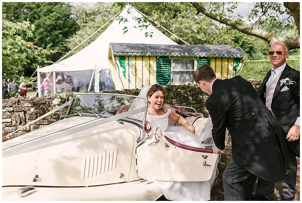 Classic Suzanne Neville Bride arriving in style | Marquee wedding at home