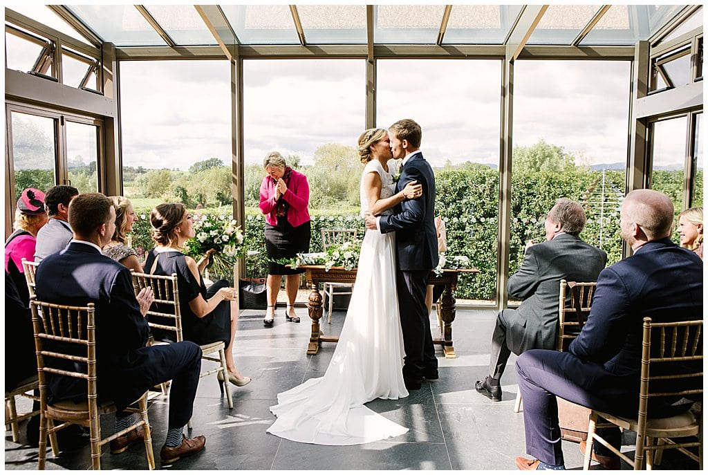 Newly married couple kiss in their small wedding ceremony at Eckington Manor