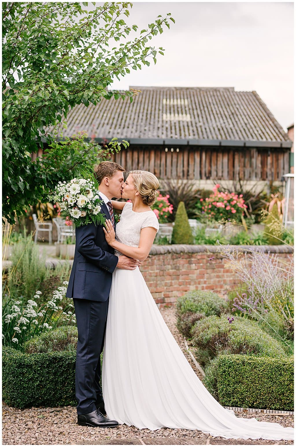 newly married couple kiss in front of a barn after their small wedding