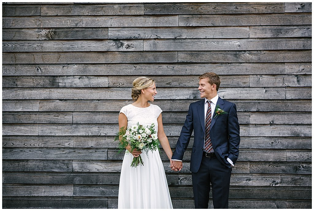 Fun, natural portrait of Bride and Groom holding hands in front of a wedding barn