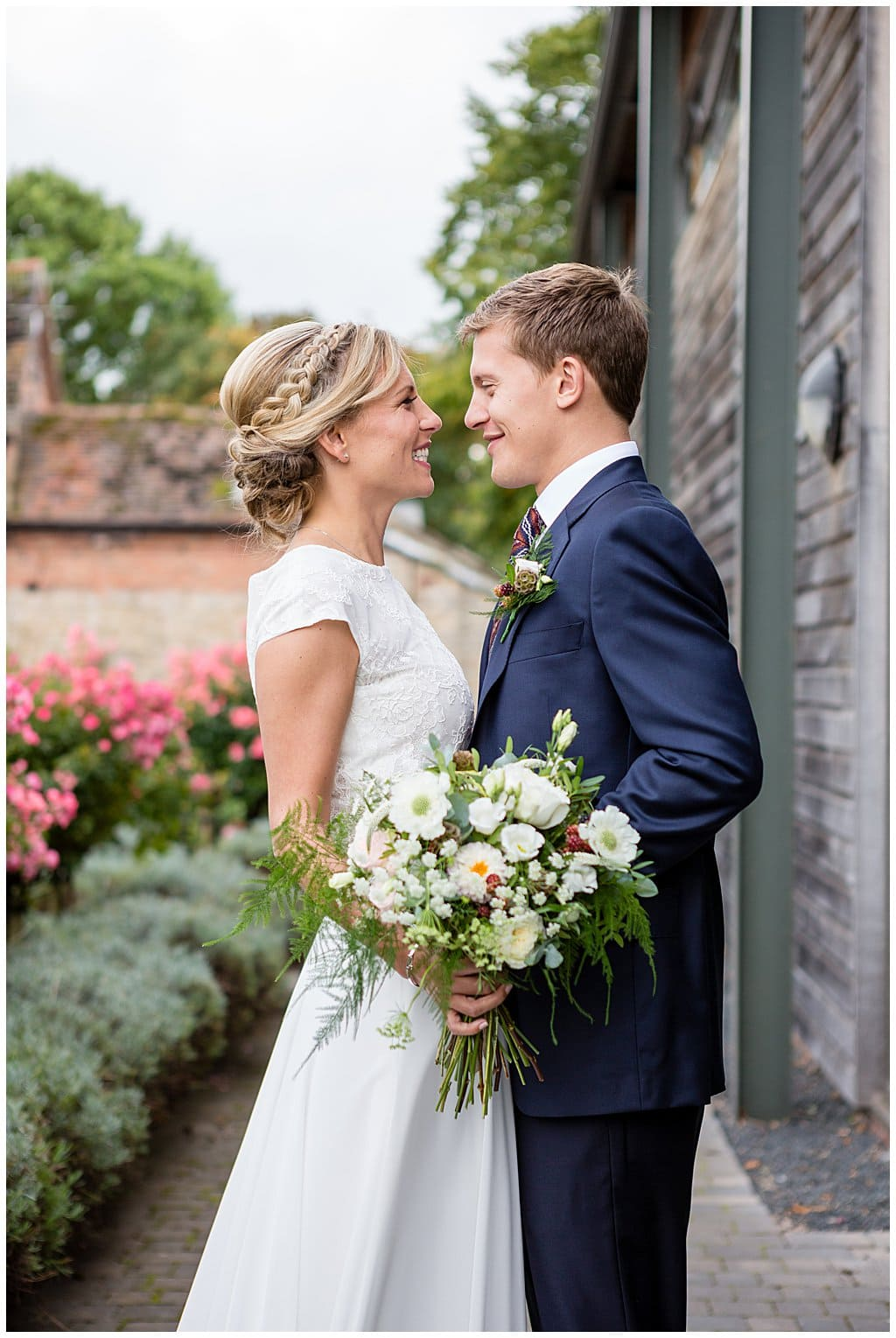 Newly married couple pose with Brides flowers outside their country barn venue