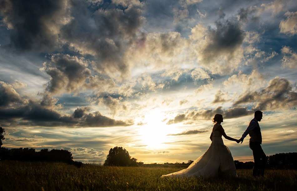 Bride and Groom walking against an epic sky